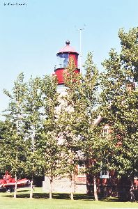 The lighthouse behind trees.